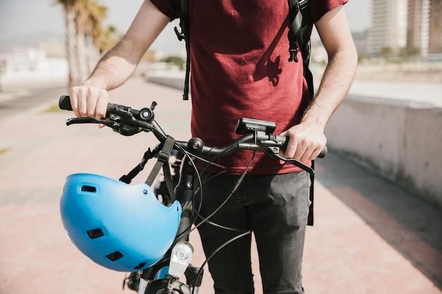 Vista frontal homem andando ao lado de bicicleta