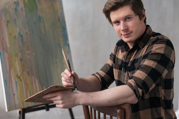 Vista frontal homem artístico posando com ferramentas de pintura