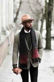 Vista frontal homem bonito casaco cinza andando lá fora