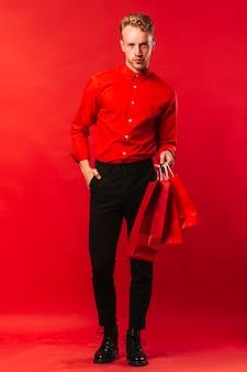 Vista frontal homem bonito com sacos de compras