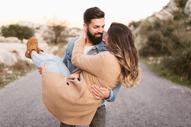 Vista frontal homem carregando sua namorada