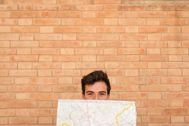 Vista frontal homem cobrindo o rosto com um mapa