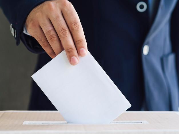 Vista frontal homem colocando uma cédula vazia na caixa de eleição