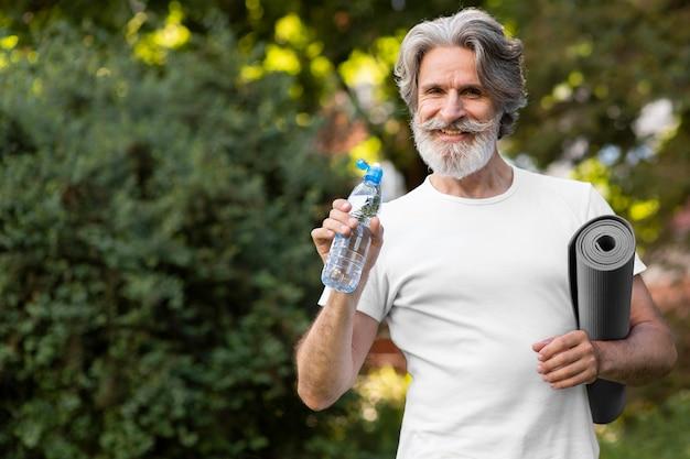 Vista frontal homem com água e tapete de ioga