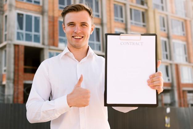 Vista frontal homem com contrato mostrando aprovação