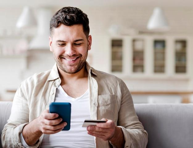 Vista frontal homem com telefone e cartão de crédito