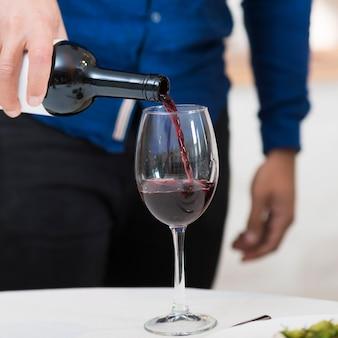 Vista frontal homem derramando vinho em um copo para sua esposa, close-up
