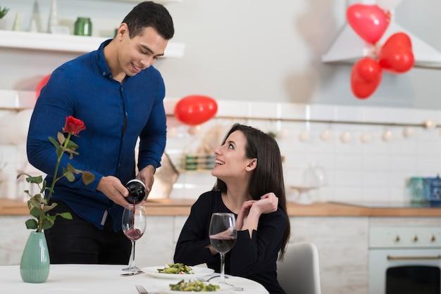 Vista frontal homem derramando vinho em um copo para sua esposa