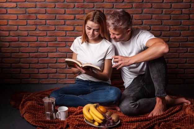Vista frontal homem e mulher lendo juntos um livro