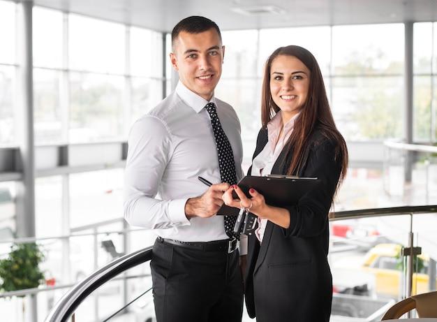 Vista frontal homem e mulher na concessionária