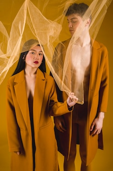 Vista frontal homem e mulher posando com um tecido transparente