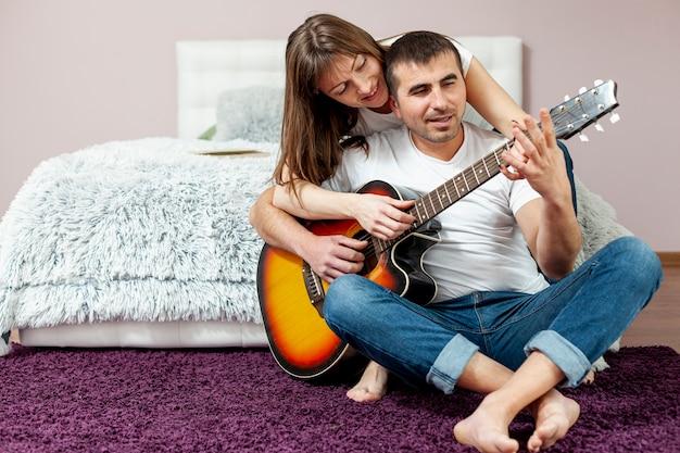 Vista frontal homem e mulher tocando violão