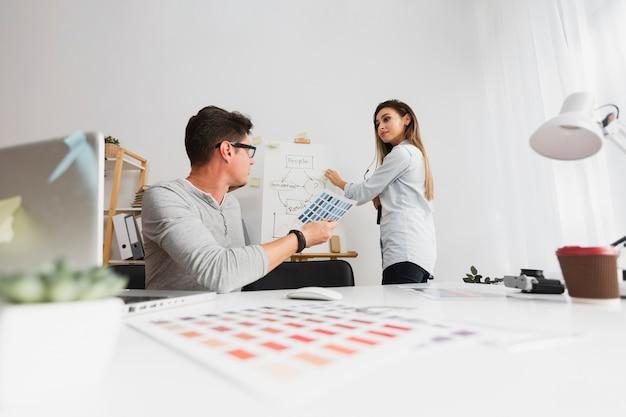 Vista frontal homem e mulher trabalhando em um diagrama