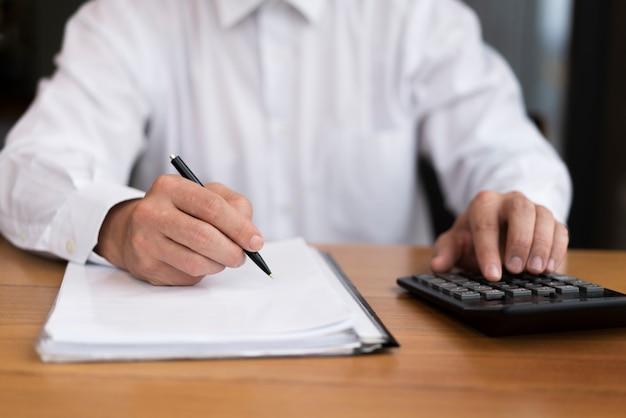 Vista frontal homem escrevendo e calculando