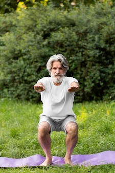 Vista frontal homem fazendo agachamentos ao ar livre