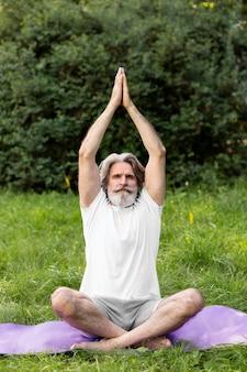 Vista frontal homem fazendo yoga fora