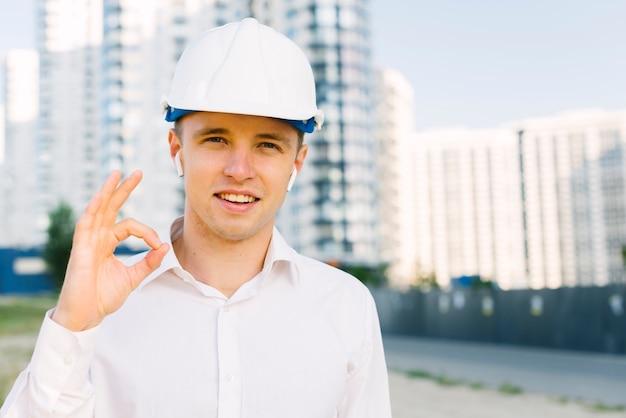 Vista frontal homem feliz com capacete mostrando aprovação