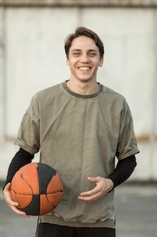 Vista frontal homem feliz com uma bola de basquete