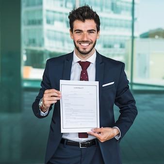 Vista frontal homem feliz segurando um contrato