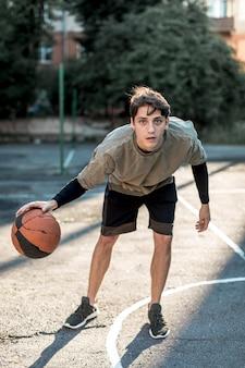 Vista frontal homem jogando basquete