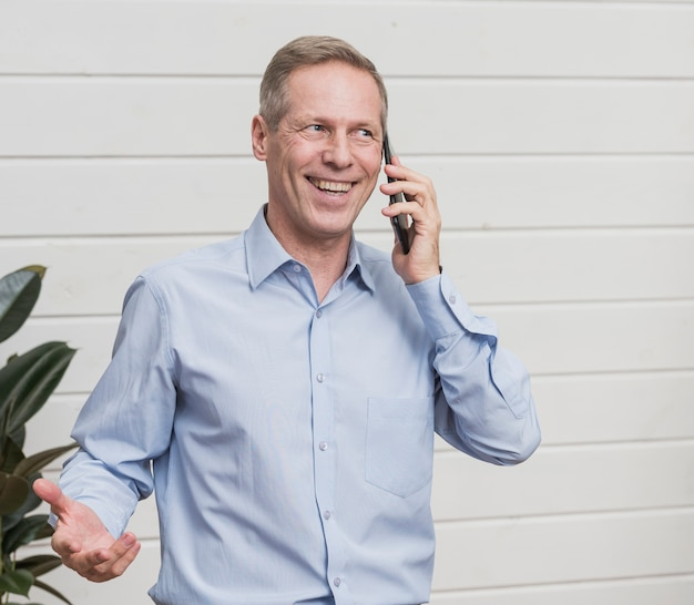 Vista frontal homem maduro, falando ao telefone