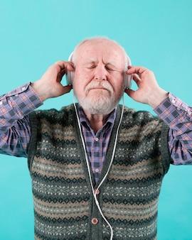 Vista frontal homem mais velho, ouvindo música