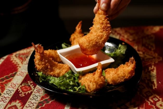 Vista frontal homem mantém camarão em massa com molho num prato