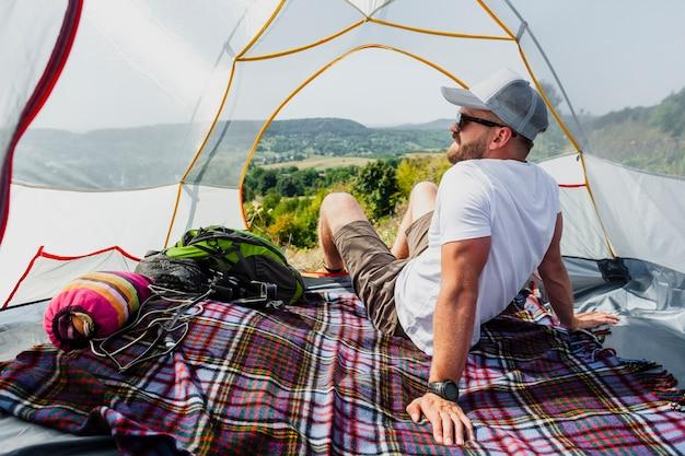 Vista frontal homem na tenda, apreciando a vista