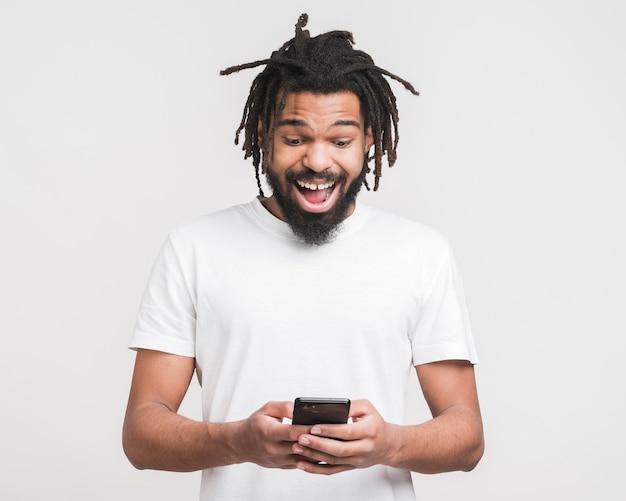 Vista frontal homem olhando em seu smartphone