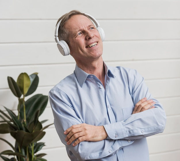 Vista frontal homem ouvindo música através de fones de ouvido