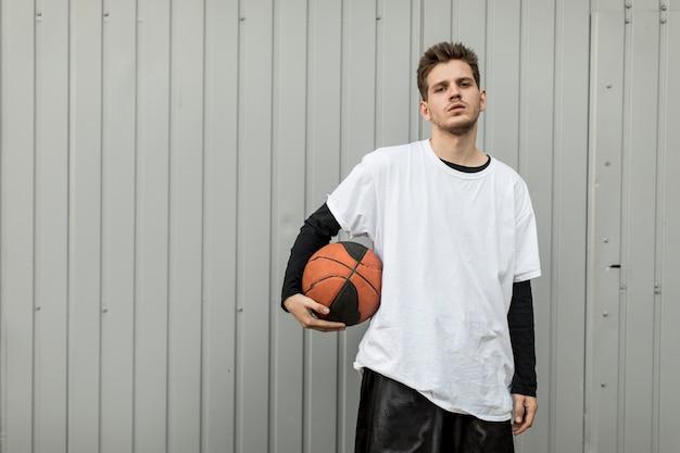Vista frontal homem posando com uma bola de basquete