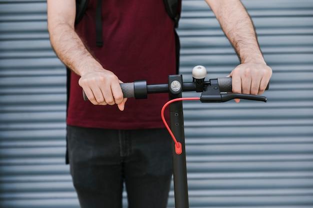 Vista frontal homem segurando alças de e-scooter