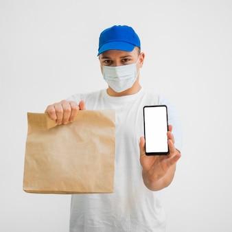 Vista frontal homem segurando o saco e telefone