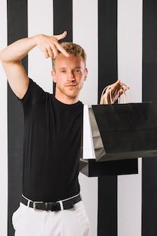 Vista frontal homem segurando sacolas de compras