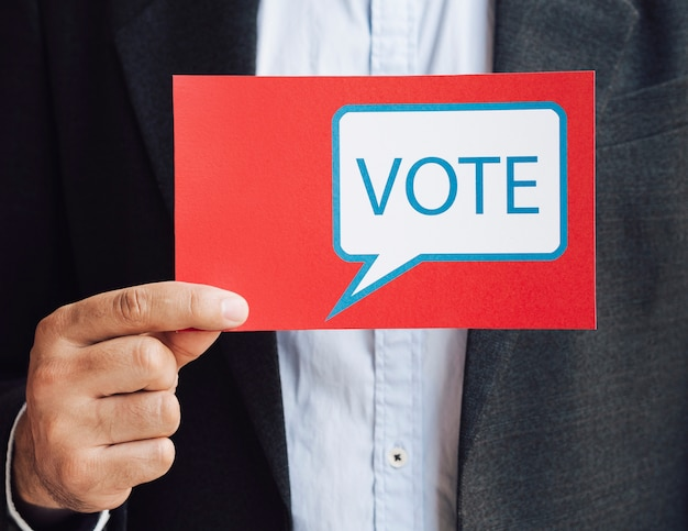 Vista frontal homem segurando um cartão de bolha do discurso de voto
