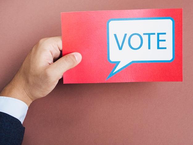 Vista frontal homem segurando um cartão vermelho com bolha do discurso de votação