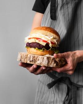 Vista frontal homem segurando um hambúrguer em uma placa de madeira