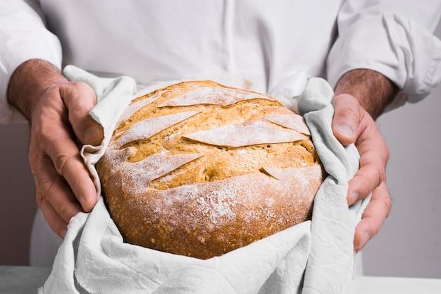 Vista frontal homem segurando um pão embrulhado