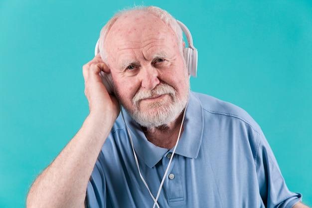 Vista frontal homem sênior com fones de ouvido
