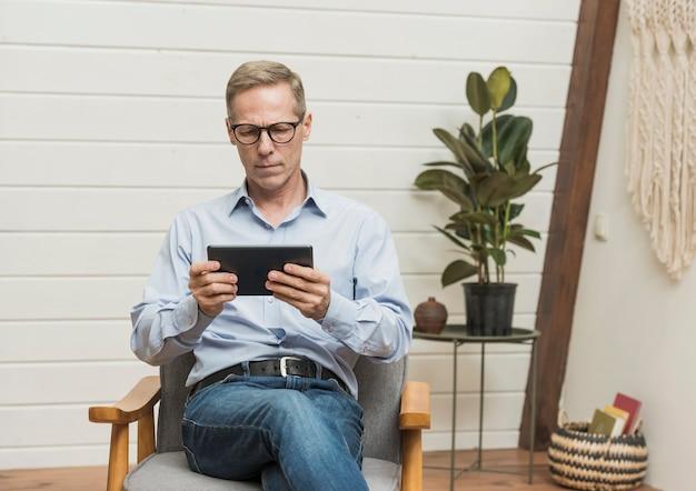 Vista frontal homem sênior, olhando através de um tablet