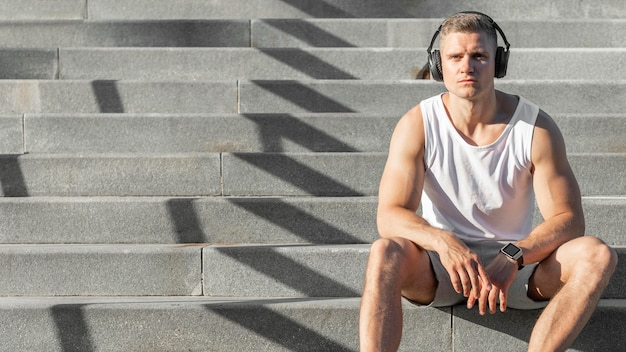 Vista frontal homem sentado na escada, com espaço de cópia