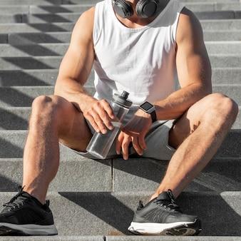 Vista frontal homem sentado na escada, segurando uma garrafa de água