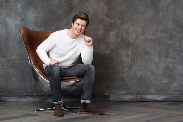 Vista frontal homem sentado na poltrona de couro com espaço de cópia
