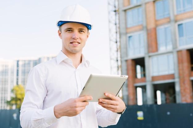 Vista frontal homem sorridente com tablet e capacete