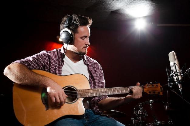 Vista frontal homem tocando guitarra e usando fones de ouvido