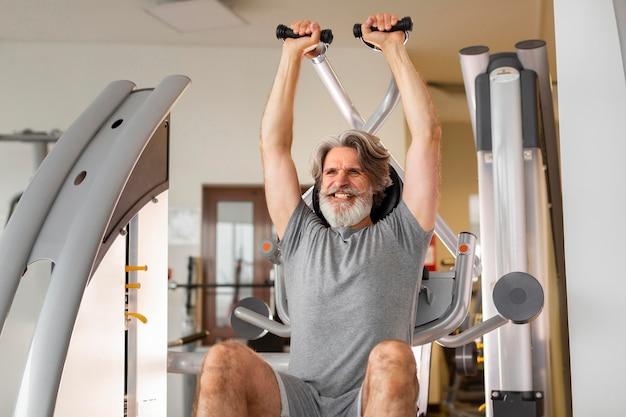 Vista frontal homem trabalhando no ginásio