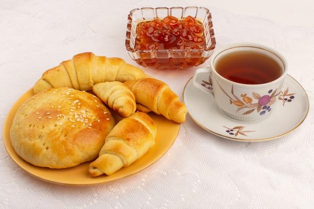 Vista frontal hora do chá croissants biscoitos geléia e chá quente no chão branco