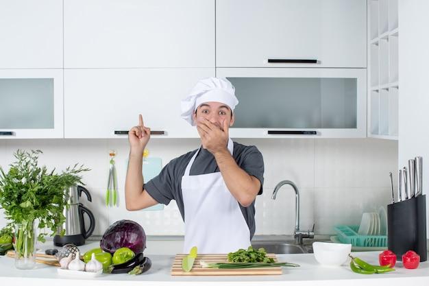 Vista frontal imaginando jovem cozinheiro de uniforme apontando para o armário