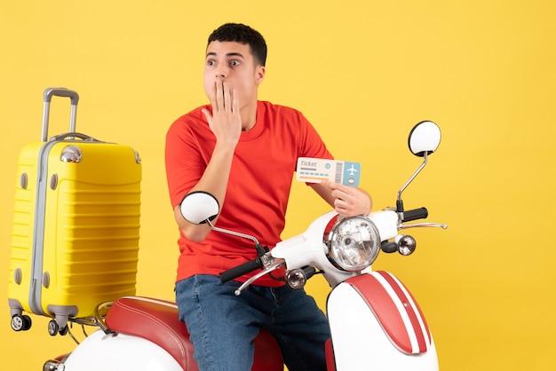 Vista frontal imaginando jovem homem com roupas casuais na motocicleta segurando o ingresso