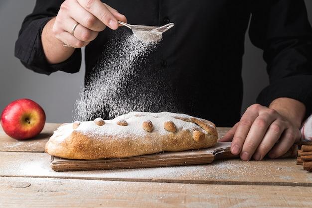 Vista frontal individual, derramando açúcar na pastelaria